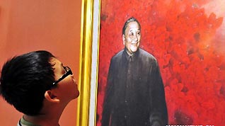 A boy looks at a painting on which Deng Xiaoping smiles in Guan Shanyue Art Museum in Shenzhen, south China's Guangdong Province, Aug. 26, 2010. The art exhibition that opened on Thusday with 90 shortlisted works aims to showcase the rapid development of Shenzhen during the past three decades since the city became a Special Economic Zone on Aug. 26, 1980.